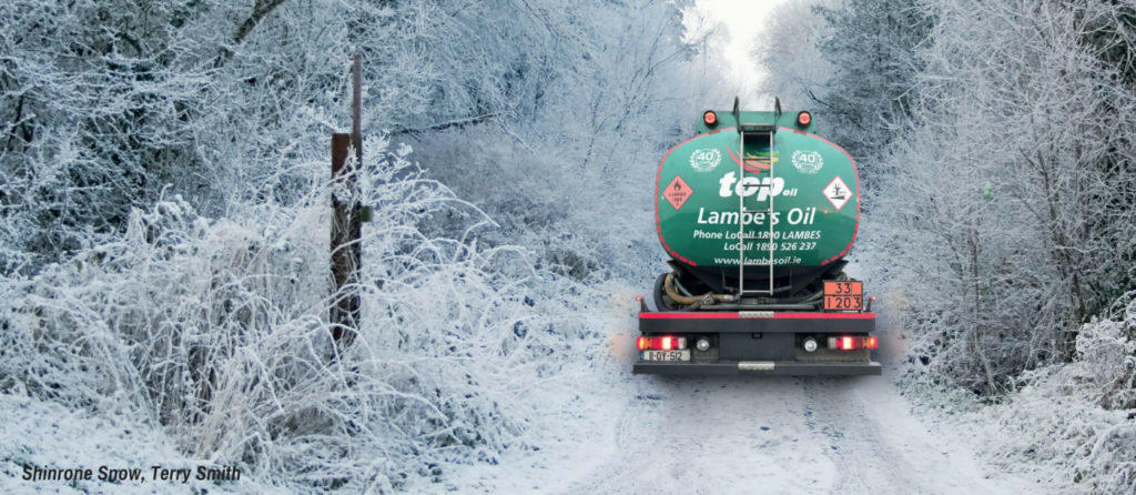 Lambes Oil delivery truck driving up a snow covered road